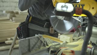 Adult worker with circular saw, cut wooden beam