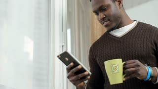 African American Man using business app on smart phone in front of the window. Handsome young businessman communicating on smartphone and drinking coffee