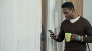 African American Man using business app on smart phone in front of the window. Handsome young businessman communicating on smartphone