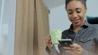 African American woman using business app on smart phone in front of the window. Young businesswoman communicating on smartphone.