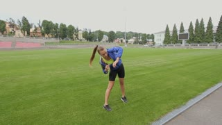 Athletic fitness woman makes a warm up before running at the sports stadium