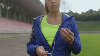 Athletic fitness woman take a break and listening music on her phone using earphones at the stadium