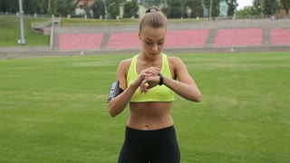 Athletic fitness woman take a break and using fitness tracker wearable technology