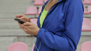 Athletic fitness woman take a break and using smartphone at the stadium