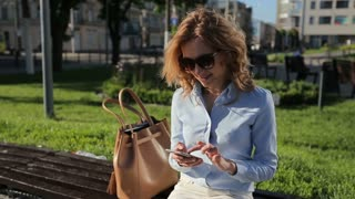 Attractive blonde business woman using smart phone in the city