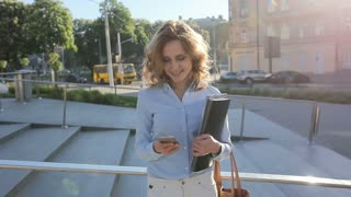 Attractive blonde business woman using smartphone commuter in city