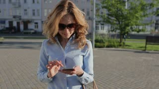 Attractive business woman commuter using smartphone in city