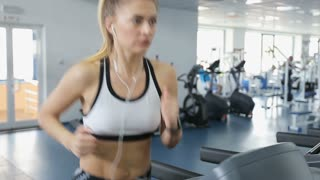 Attractive caucasian girl running on the treadmill in the sport gym with phone and earphones.