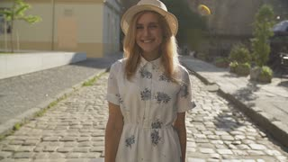 Attractive girl in hat goes down the street in a city, sun is shining, than turns to camera and smiles