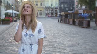 Attractive girl in hat goes down the street in a old city, sun is shining.