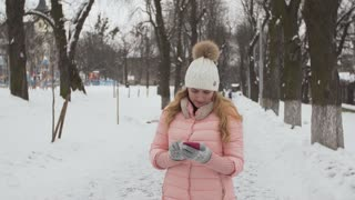 Attractive girl using phone at winter park