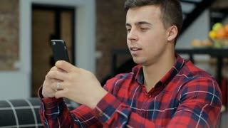 Attractive man at home using smartphone in kitchen sending message on social media smiling enjoying modern lifestyle wearing shirt