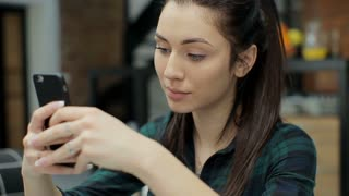 Attractive woman at home using smartphone in kitchen sending message on social media sharing and connecting with friends smiling