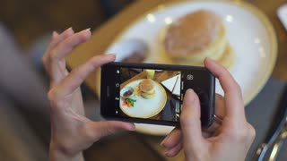 Attractive young woman Photographing food in coffee shop. closus-up