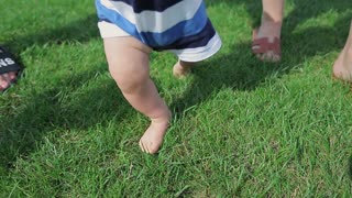Baby start walk first time and learning to walking on green grass
