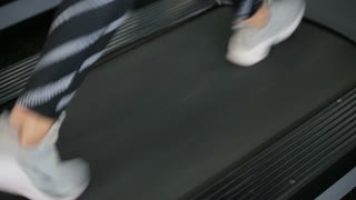 Back view of female legs walking and running on treadmill in gym, woman training