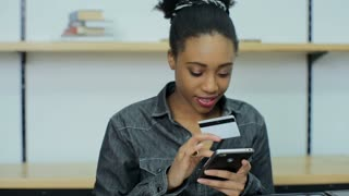 Beautiful african woman online banking using smartphone shopping online with credit card at home lifestyle