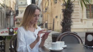 Beautiful girl drinking coffee and using smartphone in the city