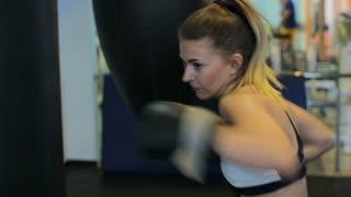 Beautiful Kickboxing woman training punching bag in fitness studio fierce strength fit body kickboxer series