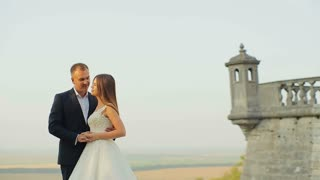 Beautiful wedding couple hugging around the old castle
