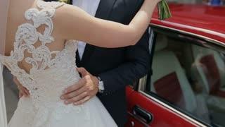 Beautiful wedding couple hugging near red car