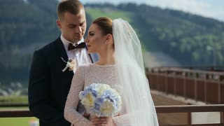 Beautiful wedding couple in mountains. Young beautiful couple bride and groom on their wedding day walking outdoors
