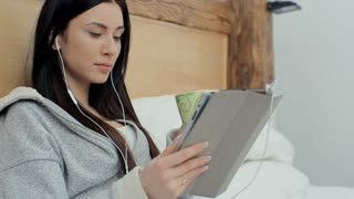 Beautiful woman at home using digital tablet technology to connect drinking coffee in bed and listen to music