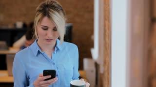 Beautiful woman drinking coffee using smartphone at the loft modern office