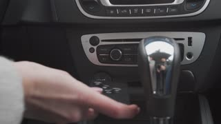 Beautiful woman hand starting a car engine with ignition key close up shot