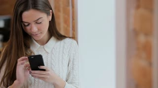 Beautiful woman using smartphone at the loft modern office. Close-up