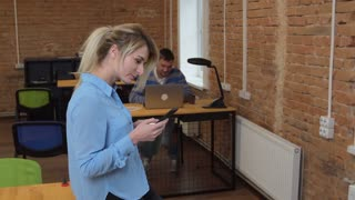 Beautiful woman using smartphone at the loft modern office