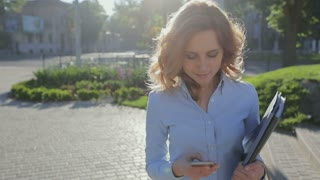 Beautiful young businesswoman wearing blue shirt and using modern smart phone while walking at break in the city, professional female employer typing text message on cellphone outside
