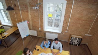 Business meeting at loft shared space. Team talking, woman manager giving direction to people. Top view.