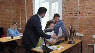 Business people working over computer in modern start up office female team leader pointing at screen discussing diverse people group teamwork using digital display technology