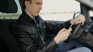 Businessman using a smartphone while sitting inside a car.