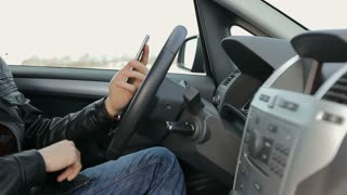 Businessman using a smartphone while sitting inside an executive black car.