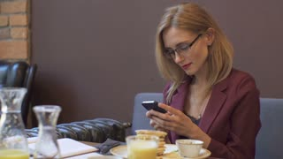Businesswoman using smartphone in Coffee Shop.