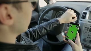 Close-up of a businessman using a smartphone with mock-up green screen in a car. Green screen.Chroma key