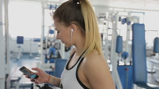 Close-up of a walking girl in the gym with a phone and a headset