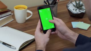 Close up of the black vertical smartphone in male hands. Fingers scrolling and taping on it. Green screen. Chroma key. Wooden office desk with cup of tea on the background.