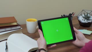 Close up of the black vertical tablet device in male hands. Fingers scrolling and taping on it. Green screen. Chroma key. Wooden office desk with cup of tea on the background