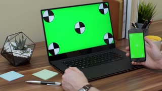 Close up of the man's hands scrolling and taping on the black smartphone with green screen and a laptop computer with green screen on the office table is on the background. Chroma key.