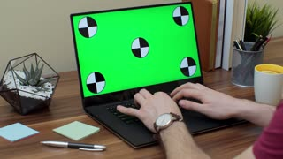 Close up of the man's hands taping on the laptop computer with green screen on the wooden table in the modern office. Indoor. Chroma key