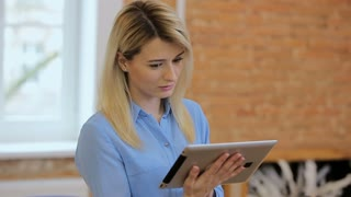 Close up of young atractive woman using black tablet at modern office.