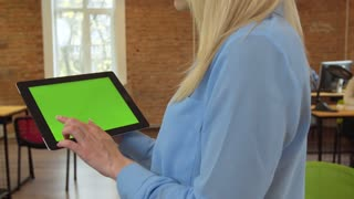 Close up of young atractive woman using black tablet with green screen at modern office. Camera stabilizer shot. Chroma key.