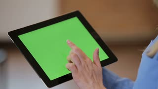 Close up of young atractive woman using black tablet with green screen at modern office. Chroma key.