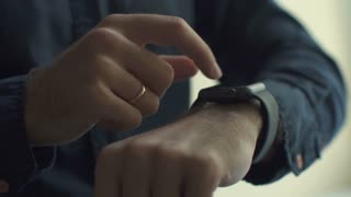 Close up of young man using smartwatch