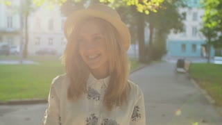 Close up portrait of beautiful young woman in hat. Romantic girl in the city park at sunrise
