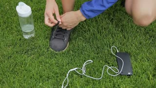 Closeup of feet of female runner getting ready tying running shoes with smartwatch, earphones and phone for music motivation for cardio workout training on athletic track in outdoor gym