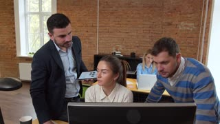 Creative business team meeting in modern start up office female team leader pointing at screen